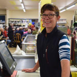 Åsa Storberg står i butikskassan, i bakgrunden en massa folk samlade runt ett bord.