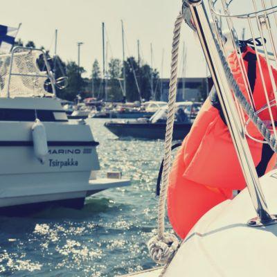 Två båtar i en glittrig gästhamn.