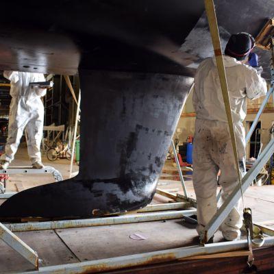 Två personer står under ett segelbåtsskrov och målar den svart.