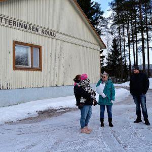 Tre personer står intill ett hus och pratar. Det är vinter. På husväggen står det Petterinmäen koulu.