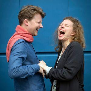 Kasvokkain olevat mies ja nainen pitävät toisiaan käsistä ja nauravat.