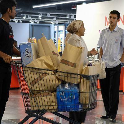 Ihmisiä ostoksilla supermarketissa.