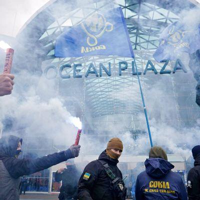 Mielenosoittajat ovat kansoittaneet Ocean Plaza -ostoskeskuksen sisäänkäynnin Kiovassa 27. marraskuuta. Sinistä savua leijuu ilmassa.