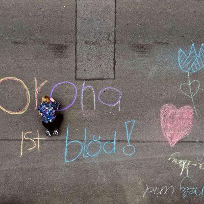 """Saksalainen lapsi kirjoittaa väriliiduilla asfalttiin """"Korona on tyhmä""""."""
