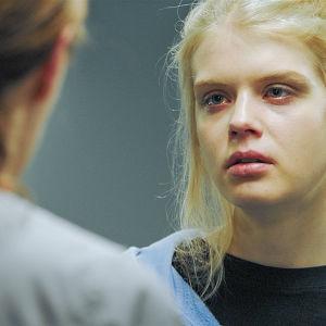 Nainen katsoo punaisin silmin sairaanhoitajaa.