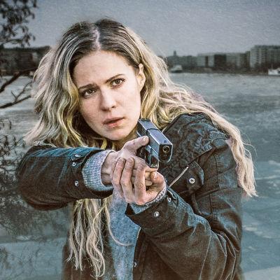 Rikostutkija Sofia Karppi (Pihla Viitala) osoittaa aseella johonkin. Hänellä on pitkät vaaleat hiukset auki, takanaan osittain jäätynyttä vettä ja kaupungin silhuettia.
