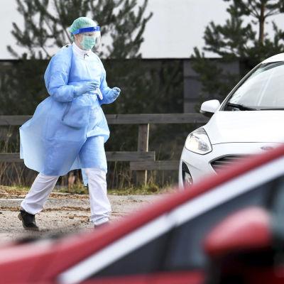 Vårdpersonal iklädd skyddsutrustning går mot vit bil för att ta ett drive-in coronatest av person.