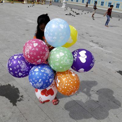 Kambodžassa köyhien perheiden lapset eivät pääse kouluun vaan joutuvat auttamaan perheitään. Tyttö myi ilmapalloja  Phnom Penhissä.
