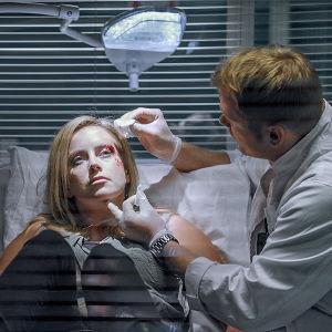 Sairaalasarja Sykkeen Iiris makaa sairaalasängyssä kasvot ruhjeilla. Lääkäri hoitaa häntä.