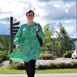 Anneli Pahta, i en grön klänning, går över ett övergångsställe.