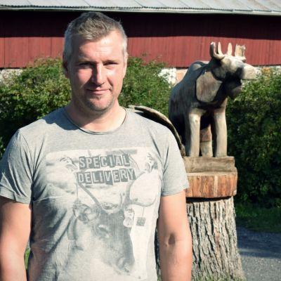 Andreas Ölander framför en ladugård.
