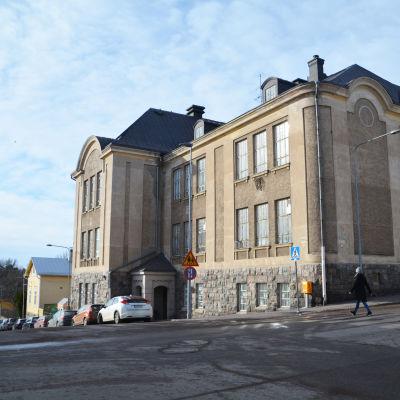 Ett stenhus i flera våningar invid en solbelyst gata.
