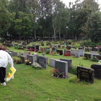 Vanhus käy hoitamssa puolisonsa hautaa.