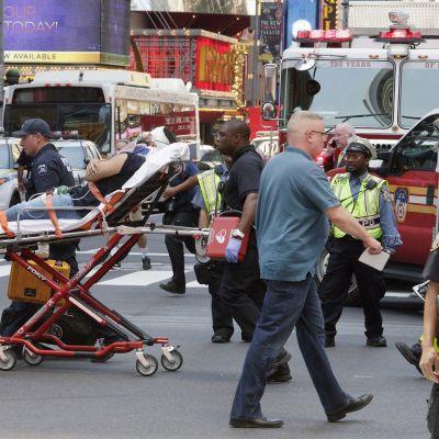 Pelastustytöntekijät vievät paareilla haavoittunutta. Ympärillä myös poliiseja.