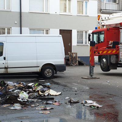 Parvekepalon jälkeen pelastuslaitoksen auto ja palanutta irtaimistoa maassa.