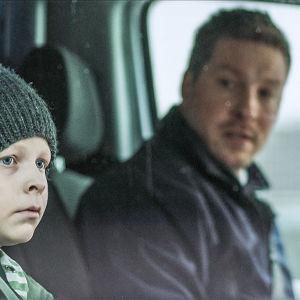 Autossa istuvat mies ja pieni poika.