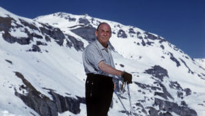 Alvar Aalto poserar med skidorna med snöklädda berg i bakgrunden.