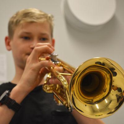 Närbild på en trumpet. I bakgrunden synns en pojke som spelar.