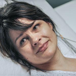 Nainen makaa sairaalasängyssä.