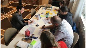 Henkilöitä kirjoittaa papereille pöydän äärellä.