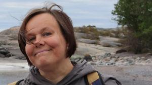 Annika Rautoma är språkstöd på Svenska Yle. På bilden är hon ute i ett klippigt landskap.