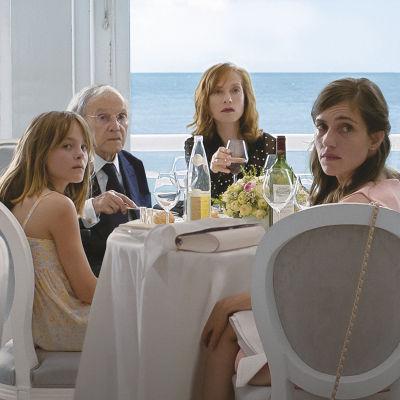 Familjen Laurent sitter vid ett middagsbord och ser förvånade ut.