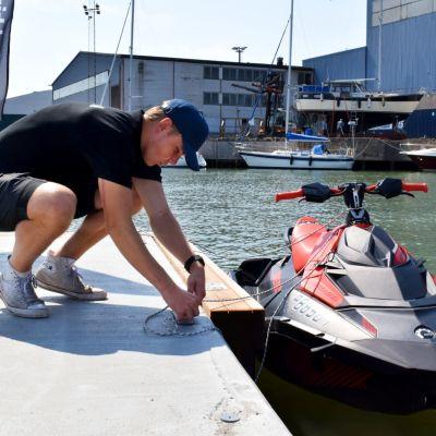 Albin binder fast en vattenskoter vid bryggan i Dalsbruks hamn.