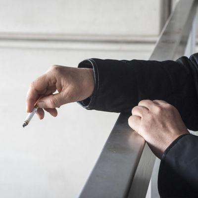 På bilden syns en hand som håller i en cigarrett. Handen ser ut att tillhöra en man som står på en balkong.