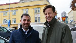 Två män står utomhus framför ett gult hus.