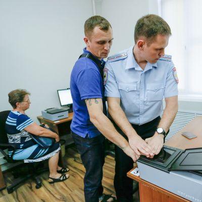 poliisi ja mies ottaa sormenjälkiä