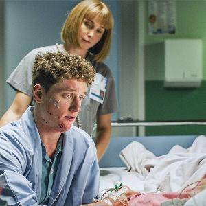 Sairaasasarjan huoneessa poika istuu sairaalasängyssä makaavan henkilön vieressä.