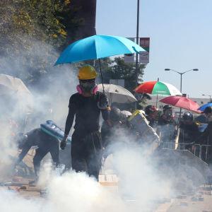 En aktivist i Hongkong i svartklädda kläder och mask håller i ett paraply och går genom ett rökmoln.