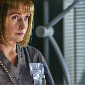Nainen, sairaanhoitaja katsoo toista ihmistä silmiin.