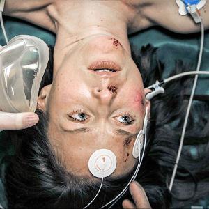 Syke-sarjan potilas makaa paareilla letkujen ja happinaamarin ympäröimänä.