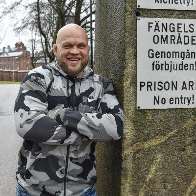 Immu Ilmen hymyilee iloisen vankilan portilla kirjoitettuaan kirjan vankien asenteista homoseksuaalisuuteen.
