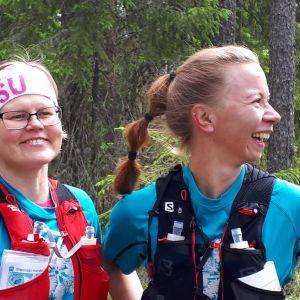 Kaksi naista hymyilee tyytyväisenä urheiluvaatteissa.