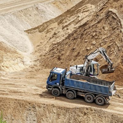 Hiekkaa siirretään kaivinkoneella kuorma-auton lavalle.