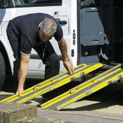 Taksinkuljettaja asettaa pyörätuoliliuskaa.