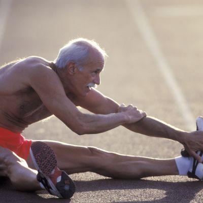 Vanha mies venyttelee yleisurheilukentällä.