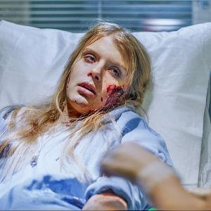 Sairaalasarjan potilas makaa sairaalasängyssä verta kasvoillaan.