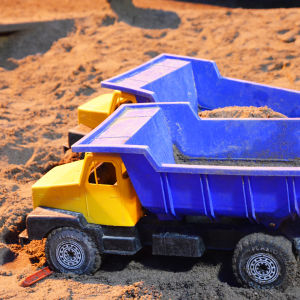 Två blågula plastlastbilar i en sandlåda. Det är mörkt ute men sandlådan lyses upp av gårdens lampor.