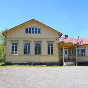 På bilden syns ett stort gult trähus med rött tak.