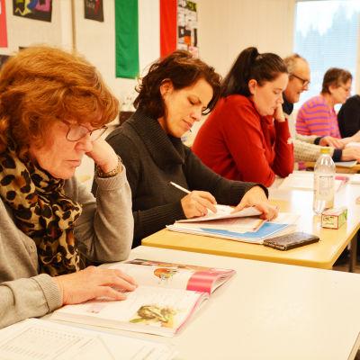 En rad med människor av olika ålder och kön sitter bakom pulpeter och koncentrerar sig på läroböckerna framför sig.