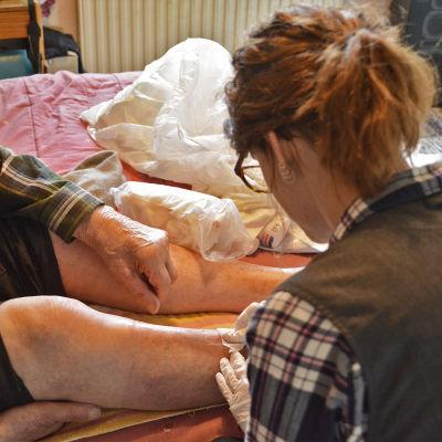 En äldre man sitter på en säng. En hemvårdare plåstrar om ett sår på hans ben.