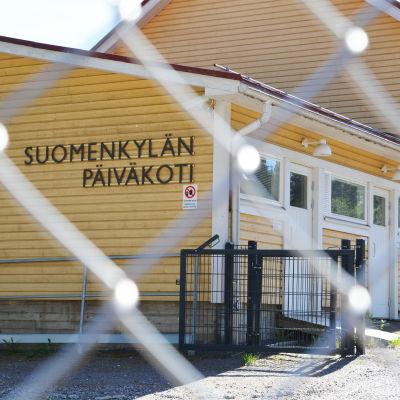 Ett gult trähus bakom ett stängsel. Det står Suomenkylän päiväkoti på väggen.