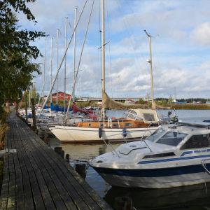 Flera småbåtar ligger förtöjda vid en brygga. I bakgrunden syns hamnbyggnader och båtar uppe på land.