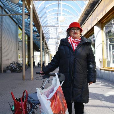 En äldre dam i svart jacka och röd hatt står bredvid en rollator. i stadsmiljö. Hon ler och tittar snett uppåt.