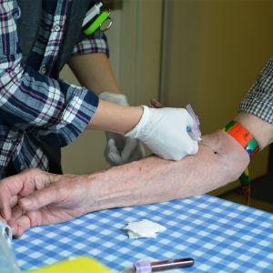 En hemvårdare tar blodprov av en äldre person. På bilden syns en bar arm och överkroppen av en person som håller på att ta blodprov med en nål.