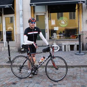 En man iklädd cykelkläder står bredvid sin cykel i gamla stan i Borgå.
