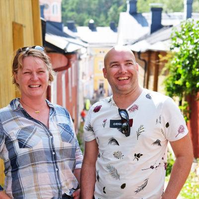 En kvinna och en man står framför kameran och ser glada ut i ett somrigt Borgå. Bakom dem syns röda och gula trähus i Gamla stan i Borgå.